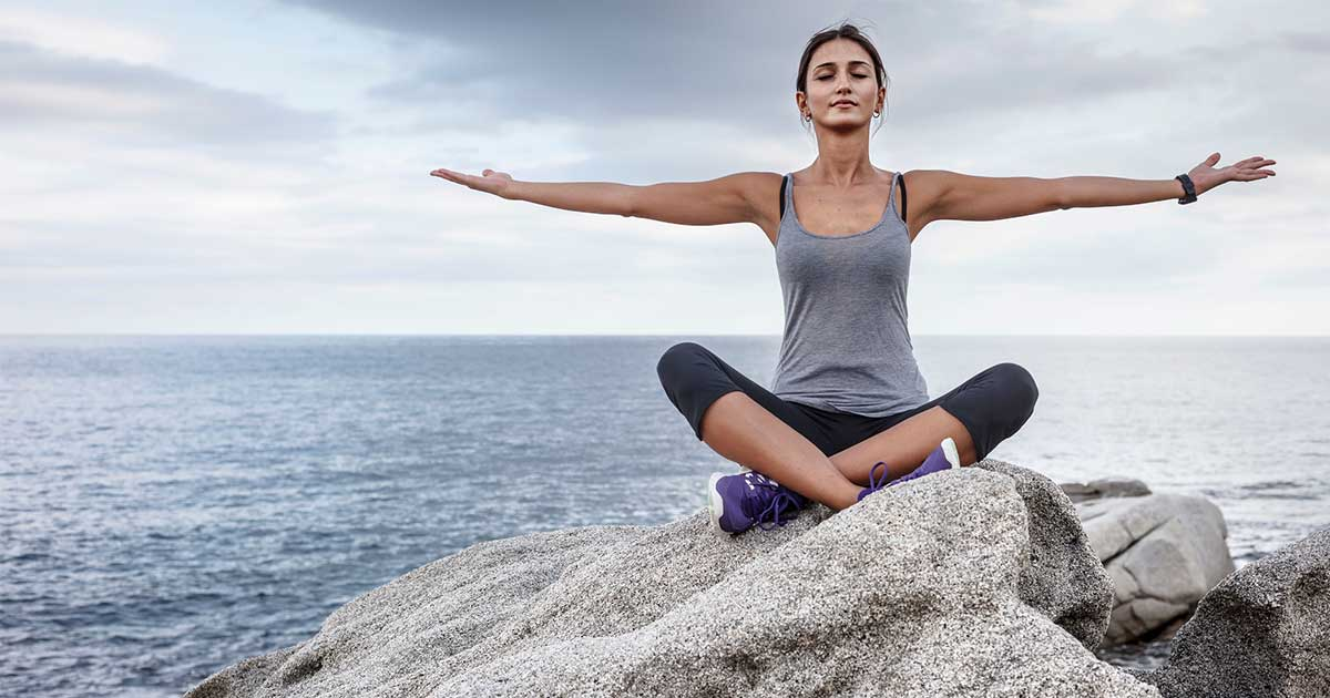 a woman relieving stress by meditating on a boulder by the water, an example of eczema lifestyle changes