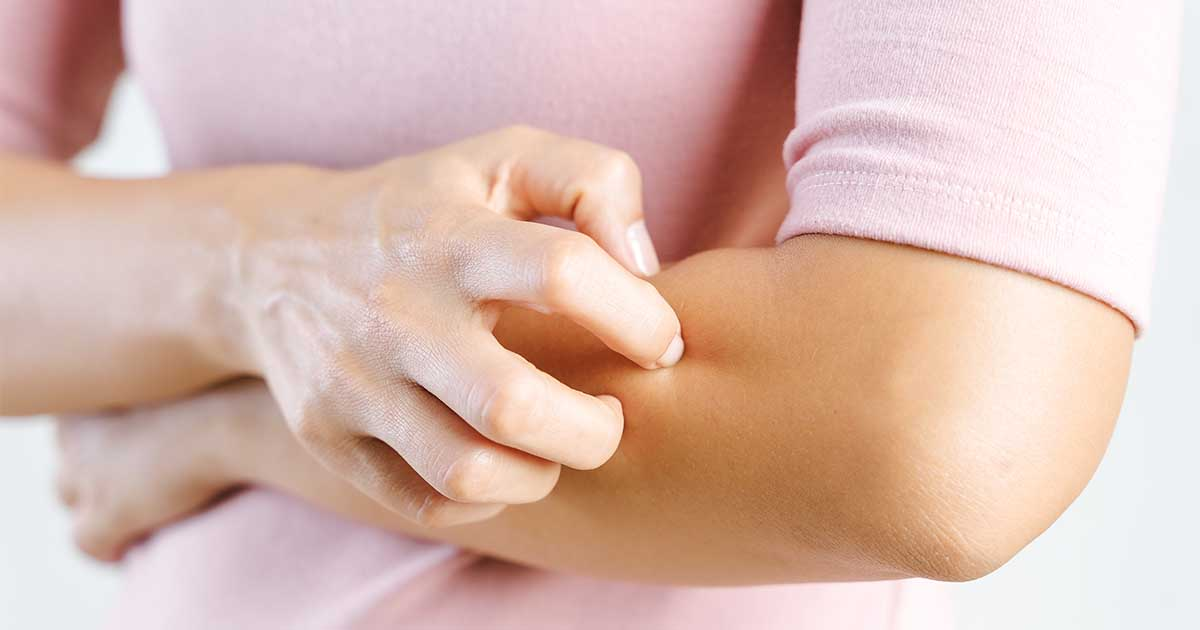 A woman wearing a pink shirt while itching the skin on her arms.